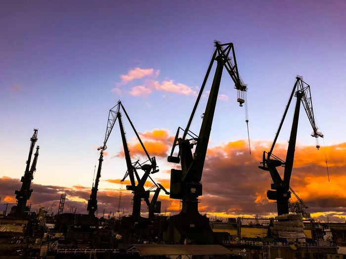 Low angle view of cranes against sky during sunset