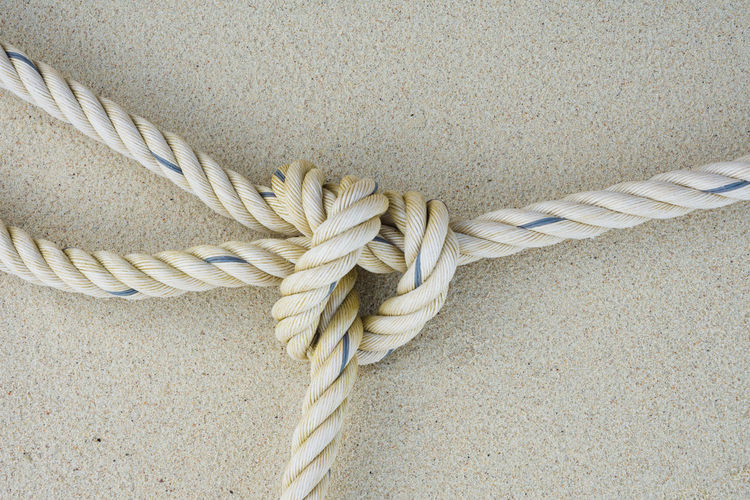 Close-up of tied rope against wall