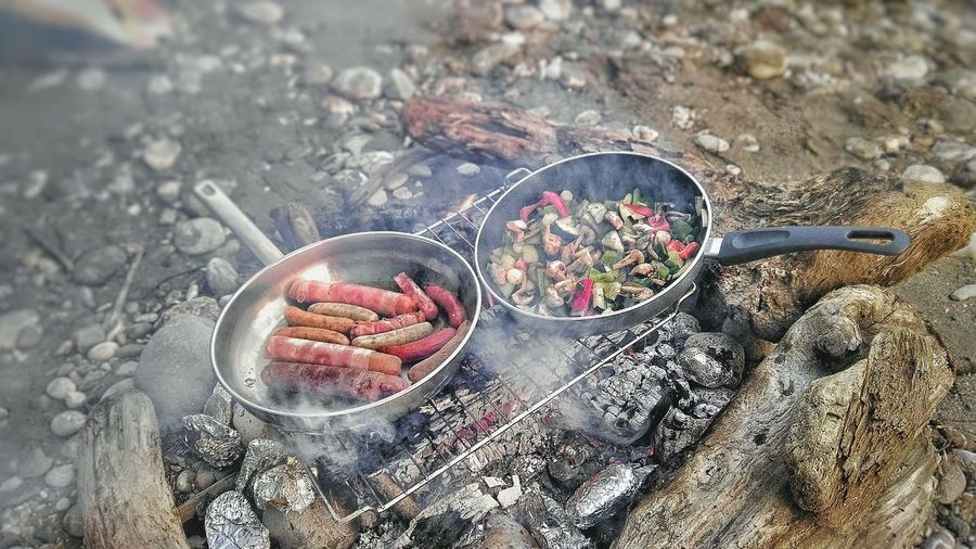 High Angle View Of Sausages And Vegetables Being Cooked On Campfire