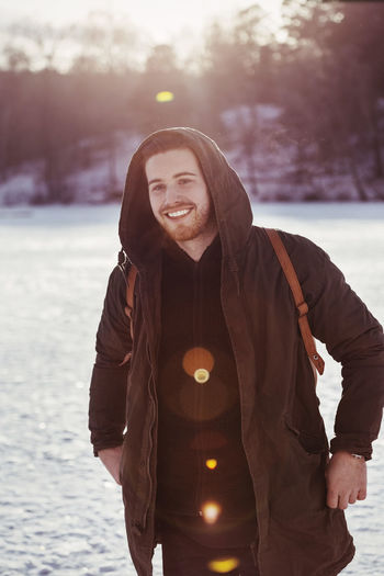 Portrait of smiling standing against snow during winter