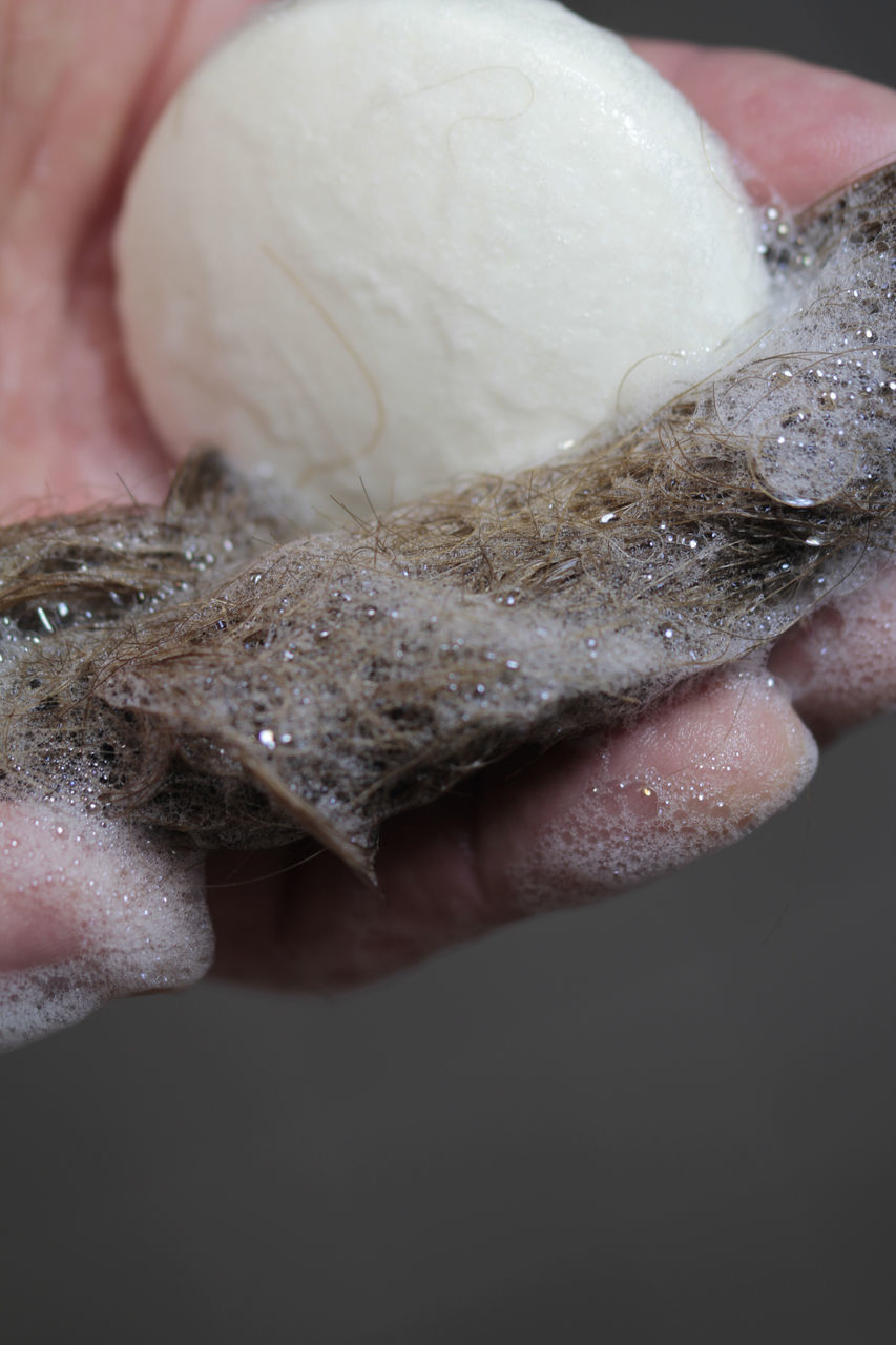 CLOSE-UP OF HUMAN HAND HOLDING ICE CREAM