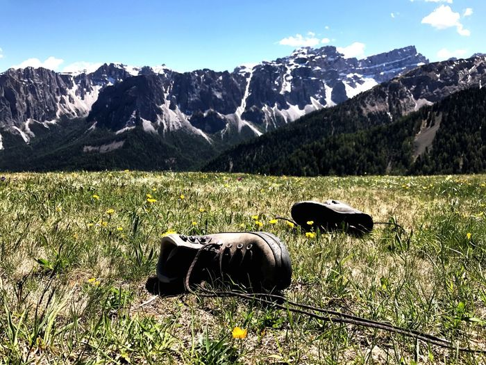 Hiking boots are laying in the gras in front a Mountain Panorama in the South Tyrolean alps Mountain Nature Grass Day Mountain Range Beauty In Nature Scenics Tranquility Outdoors No People Landscape