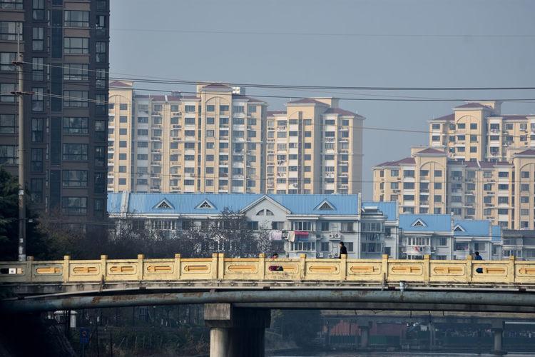 Train on bridge against buildings in city