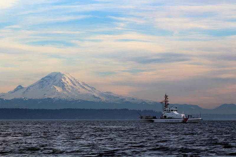 Boat sailing in river against mt rainier and cloudy sky at dusk