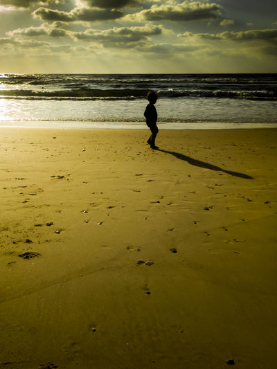 A kid saying farewell to the ocean at the end of the summer. Godrays Mediterranean  Sunlight At The Beach Beach Child Clouds And Sky Evening Farewell Kid Long Shadow - Shadow Melancholy Ocean Real People Sad Sadness Sea Shadow Shells Sillouette Sunset Vacation Water Waves, Ocean, Nature