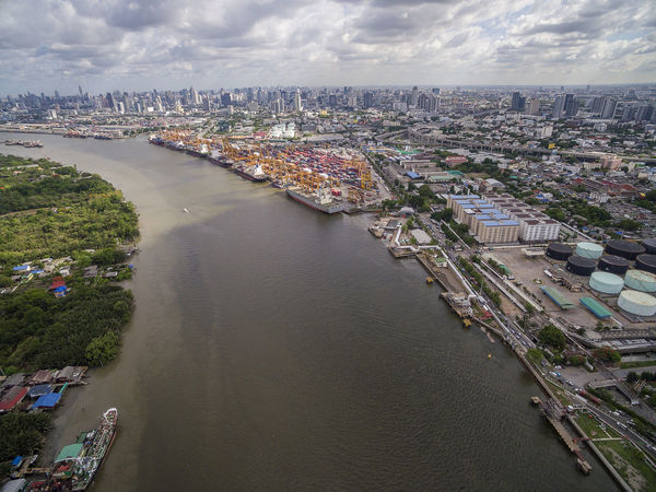 Aerial View Above the Bangkok Dockyard by the Chao Phraya River with Cargo Ships Waiting to be Upload and Offload Cargo Containers Bangkok Dockyard Cargo Ship ่Chao Phraya River Container Ship Container Port Dockland Dockyard Shipping Containers Shipping Industry Aerial Photography Architecture Cargo Container Cargos Loader Cargoship City Container Loading Containers Stacks Docklands Marshland  Offloading Outdoors Port Riverscape Transportation