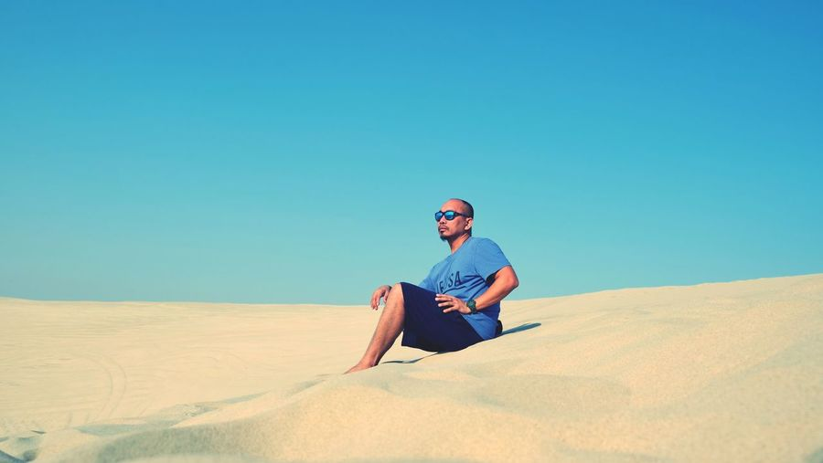Full length of young man sitting on sand