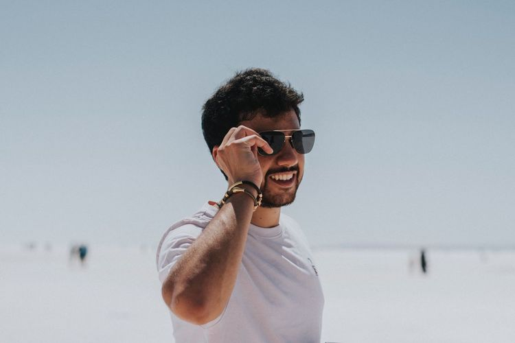 Millenial Stylish Plain Background One Person Glasses Young Men Young Adult Sunglasses Fashion Standing Casual Clothing Lifestyles Waist Up Leisure Activity Headshot Men Happiness Real People Portrait Smiling This Is Natural Beauty The Modern Professional