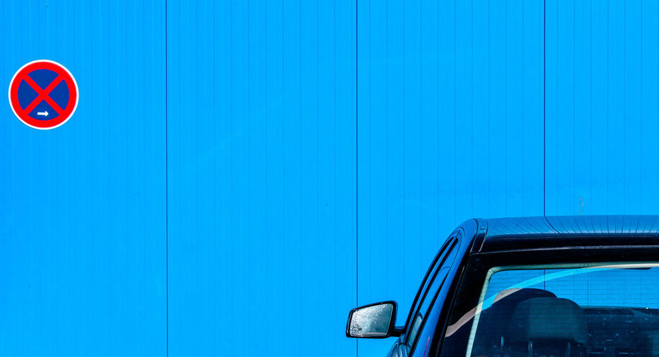 Close-Up Of Car Parked By Blue Wall