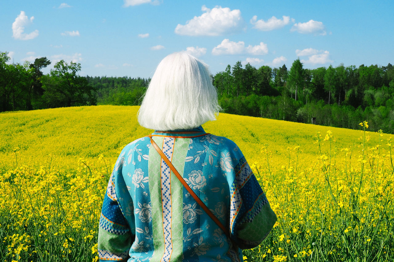 Rear View Of Senior Woman Standing On Rapeseed Field Against Sky
