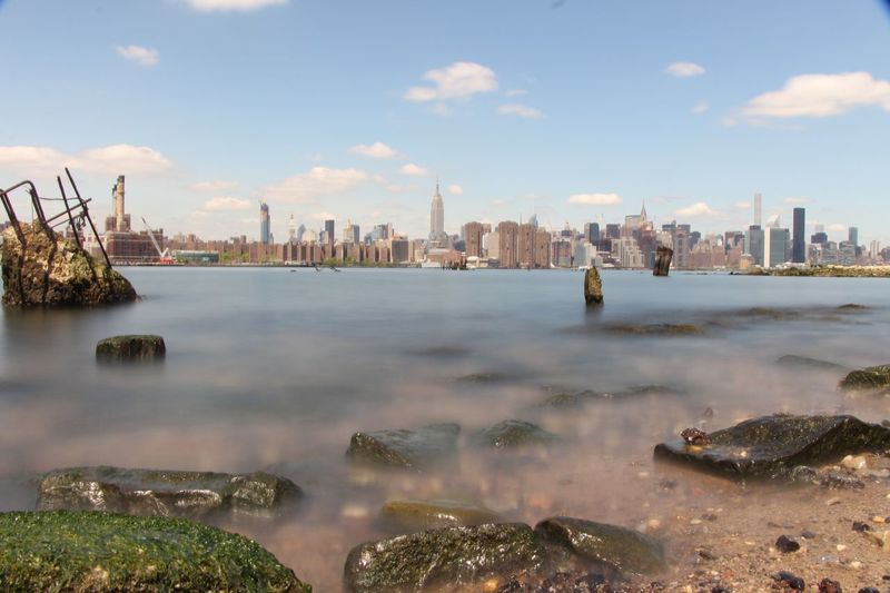 Distant View Of Manhattan Skyline Seen From River