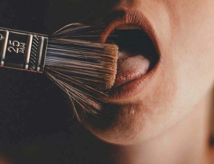 Close-up of person licking paintbrush