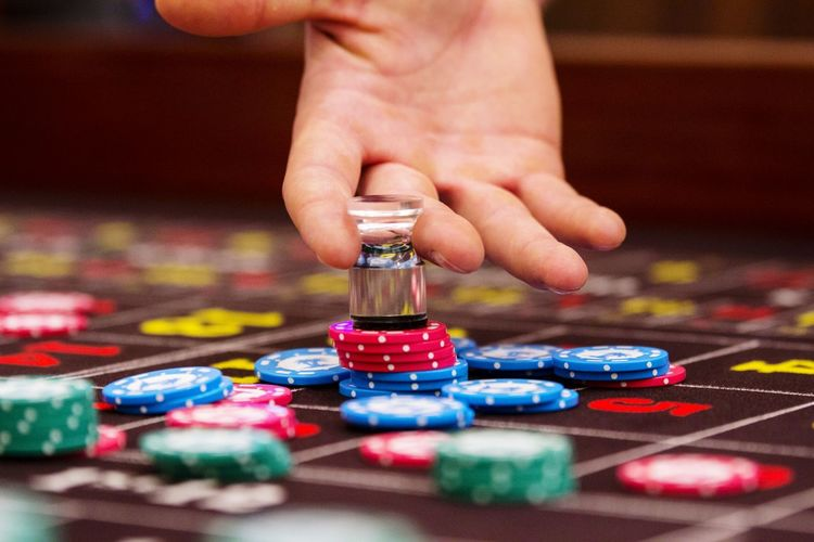 Cropped Hand Of Man Playing With Gambling Chip