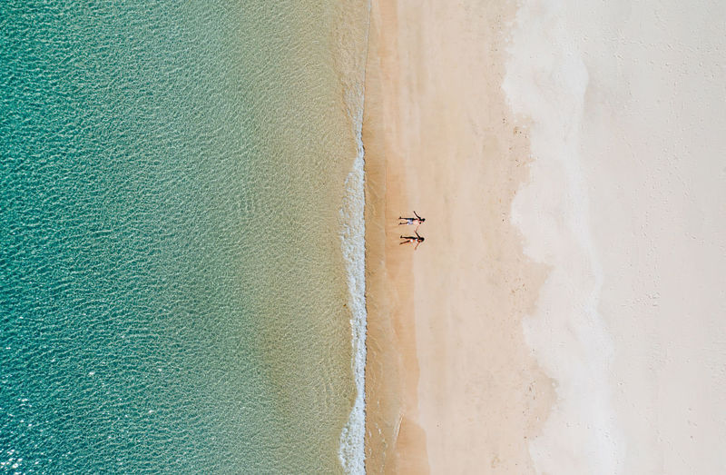 Drone view of couple at beach on sunny day