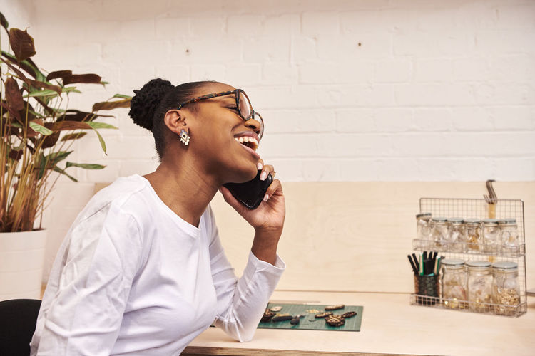 Smiling businesswoman talking on phone while sitting at office