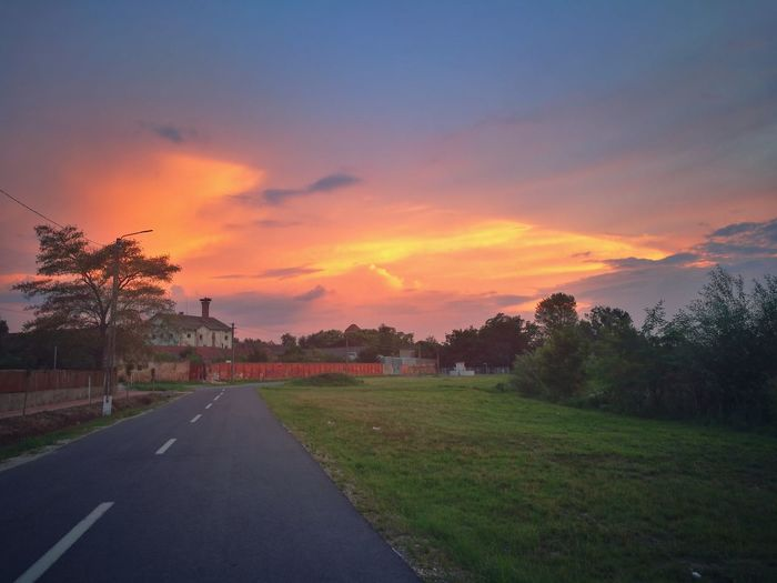 Sky Plant Sunset Road Transportation Tree Nature Cloud - Sky Direction Scenics - Nature No People The Way Forward Beauty In Nature Grass Landscape Tranquility Tranquil Scene Orange Color Symbol Environment Diminishing Perspective Outdoors