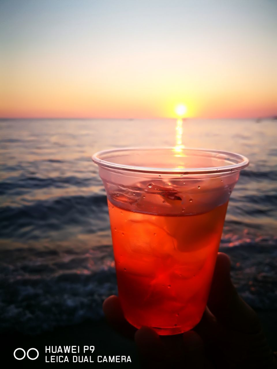sky, drink, refreshment, sunset, sea, food and drink, glass, orange color, water, beach, nature, focus on foreground, drinking glass, beauty in nature, household equipment, scenics - nature, close-up, horizon over water, freshness, outdoors, cocktail