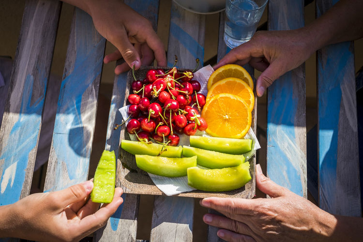 Cropped hands of people with fruits on table
