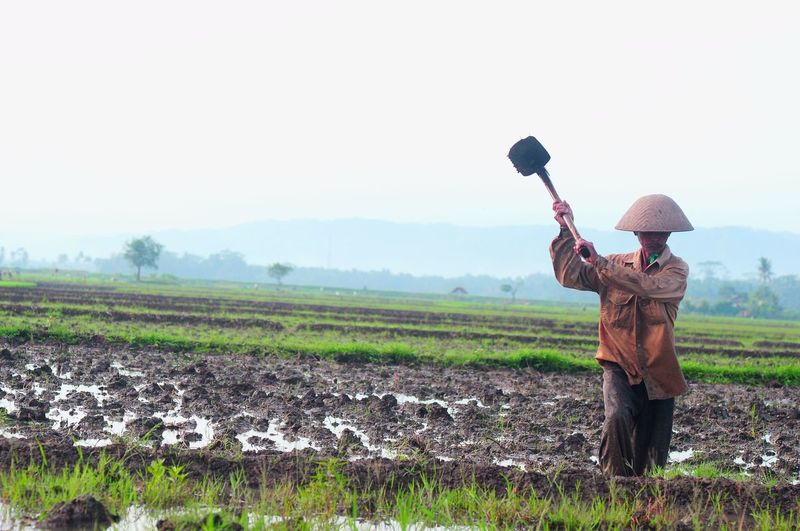 Man Working On Farm Against Sky