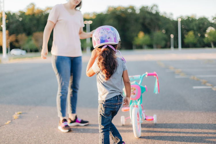 Mother and daughter standing by bicycle on road