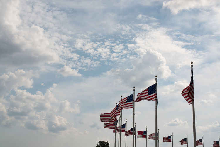Low angle view of american flags waving against cloudy sky