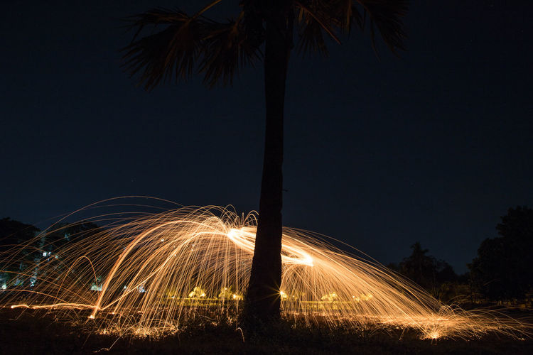 Light trails on beach against sky at night