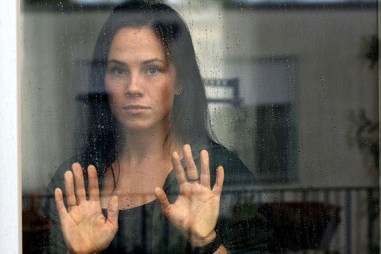 Portrait of woman looking through glass window