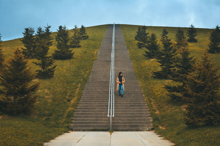 Woman moving down on steps amidst plants against sky