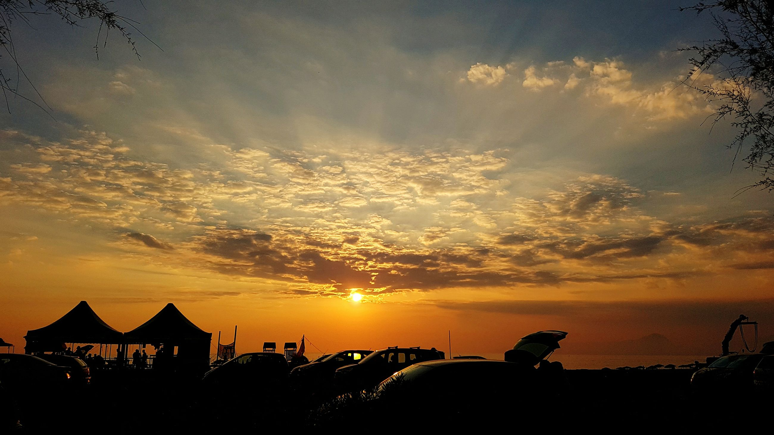 sunset, silhouette, vacations, tranquil scene, beach, scenics, sun, tranquility, sky, idyllic, tourism, thatched roof, orange color, cloud - sky, tourist, architecture, sea, cloud, beauty in nature, water, dramatic sky, atmosphere, majestic, sunshade, nature, outdoors, moody sky, dark, atmospheric mood, back lit