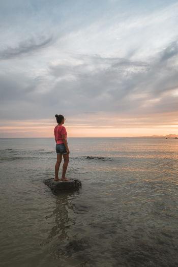 Full length of man on beach against sky during sunset