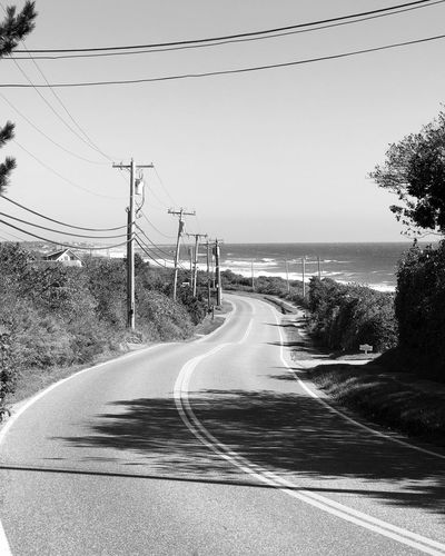 Beach Road Transportation Cable Connection The Way Forward Power Line  Day Nature Electricity Pylon Outdoors No People Motion Speed Curve Electricity  Sky Tree Scenics Clear Sky Winding Road Beach ocean Waterfront Water Wave Surfing
