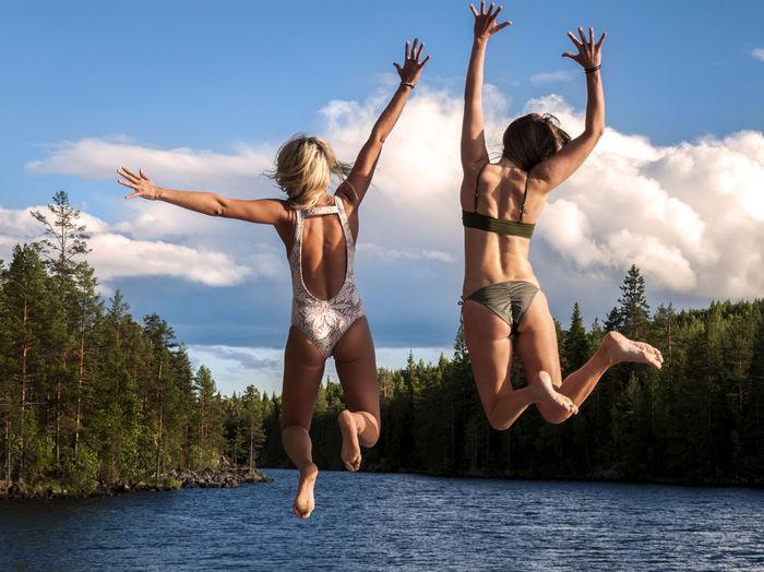 Full Length Of Female Friends Jumping Into Lake Against Sky