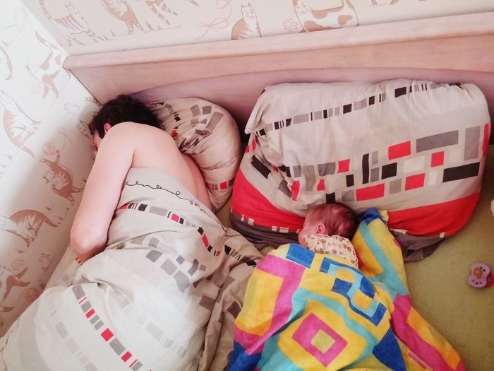 High angle view of father with daughter sleeping on bed at home