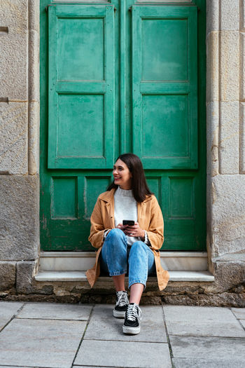 Full length of teenage girl sitting at entrance of building