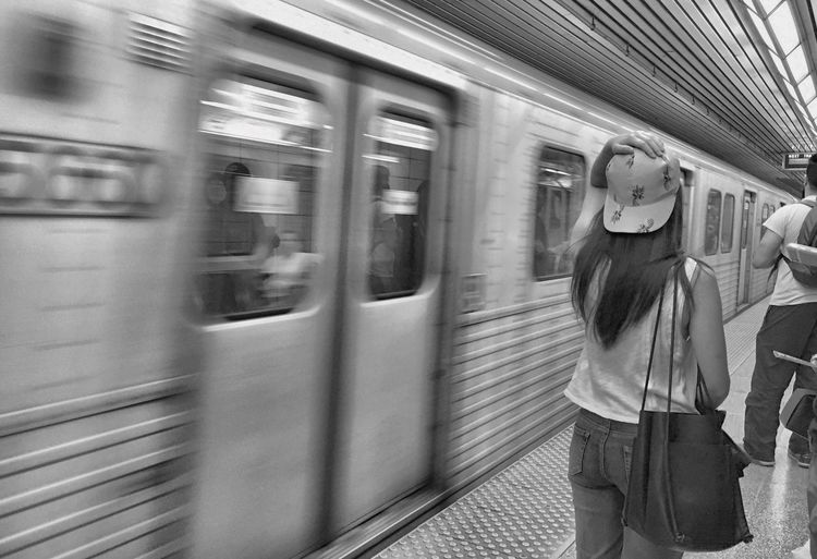 Rear view of woman standing on platform by metro train