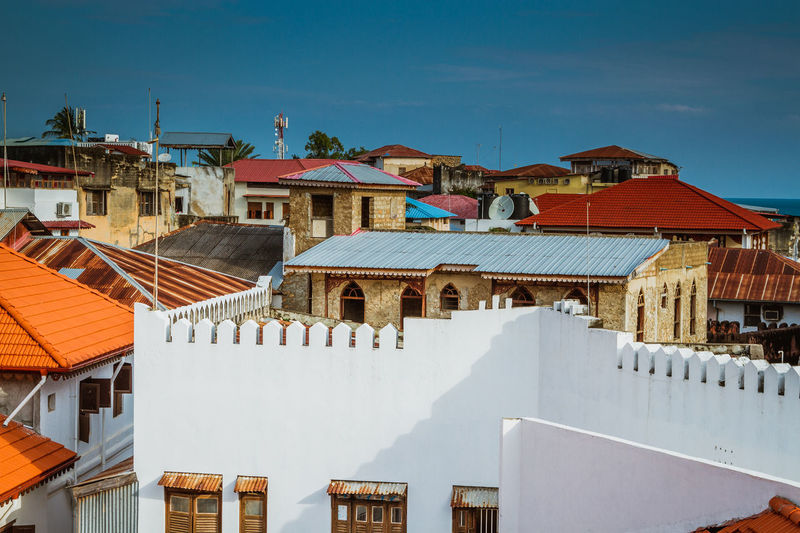 Checked into the hotel room and saw this scene of Stone Town rooftops in Zanzibar and knew I had to capture the moment. Architecture Building Exterior Built Structure Clear Sky Copy Space Copy Space Over Buildings Day House No People Orange Color Outdoors Roof Sky The Architect - 2017 EyeEm Awards Zanzibar_Tanzania Zanzibar🏊🏄🎣