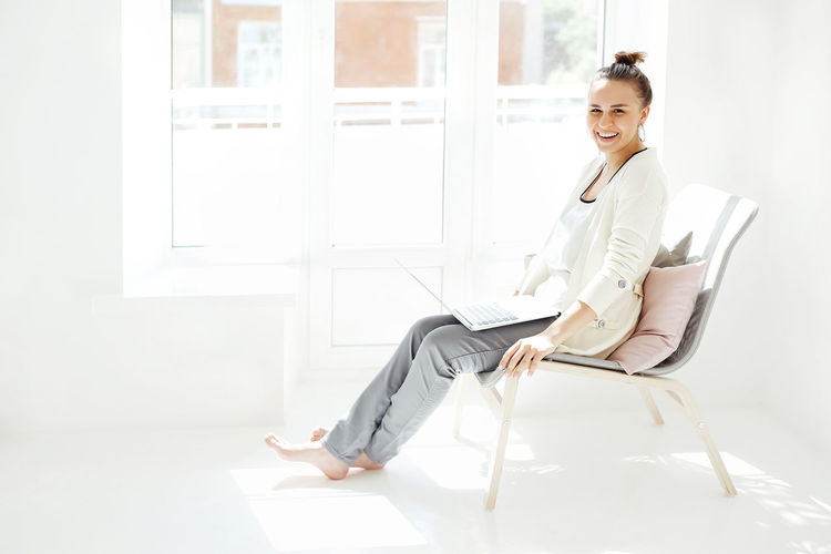 Portrait of a smiling young woman sitting on chair