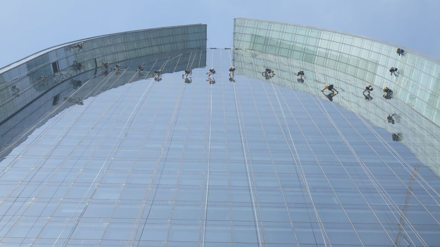 Low angle view of window washers on modern building