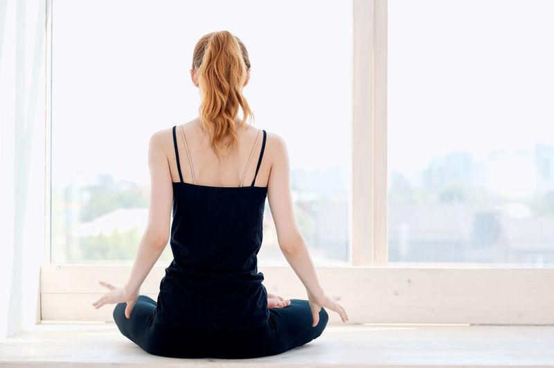 Rear view of woman sitting in window