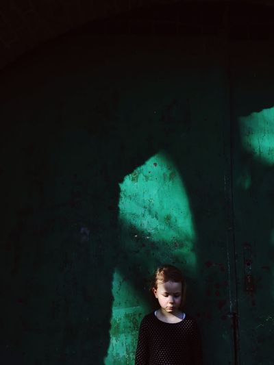 View Of Young Girl Against Green Wall