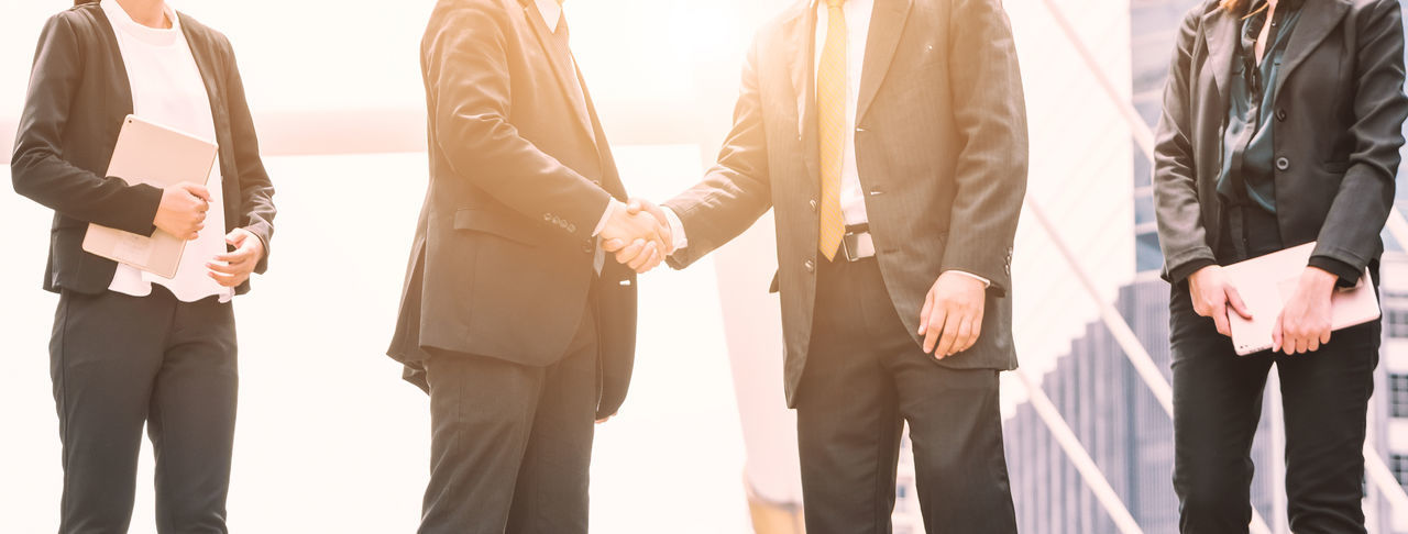Midsection Of Businessmen Shaking Hands With Colleagues In City