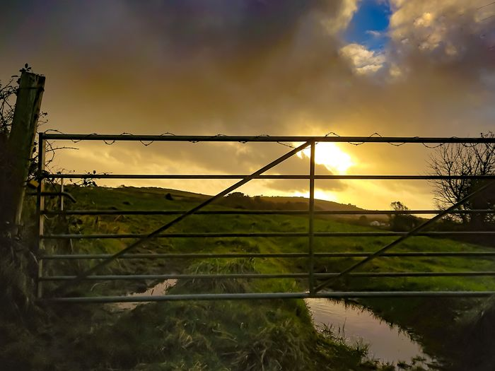 A tranquil rural scene Gate Grass Field Ruralscapes Rural Scenes Rural Landscape Rural_living Agricultural Land Agriculture Farming Countryside Countrylife Water Sunset Sky Barbed Wire Nature Cloud - Sky Outdoors Rural Scene No People Agriculture Beauty In Nature Day