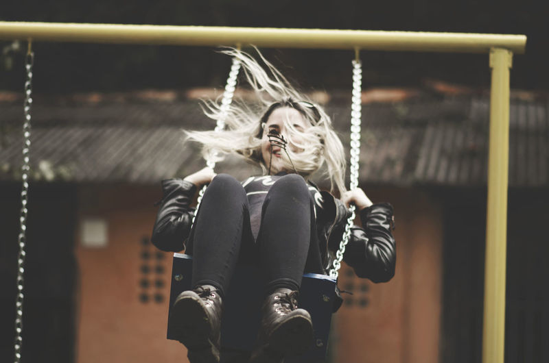 Cheerful young woman swinging at playground