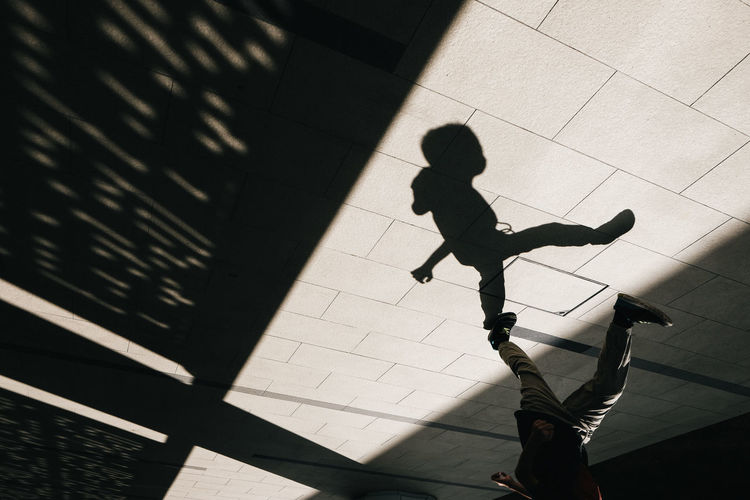 High angle view of silhouette people walking on tiled floor