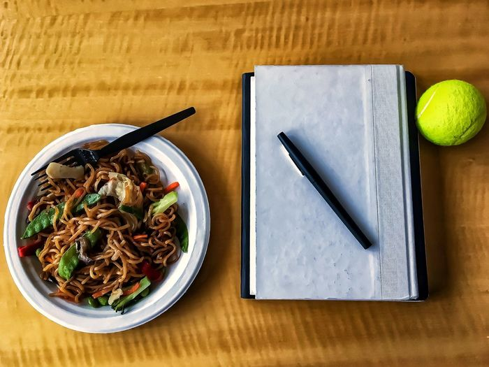 Lunch in the office with Japanese noodle and veggie stir fry, book, notebook, pen, and yellow tennis ball. Pea Pod Inside Desktop Colors Marker Rice Noodles Noodles Meal Veggies Stir Fry Wood Desk Yellow Tennis Ball Ball Notebook Book Pencil Office Indoors  Table High Angle View Food And Drink No People Healthy Eating Close-up Food Freshness Ready-to-eat Day Modern Workplace Culture