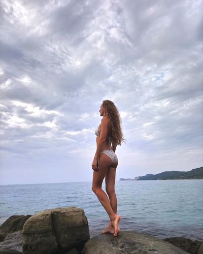 Young bikini woman standing on rock at sea shore against sky