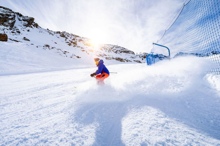 Snow Winter Cold Temperature One Person Leisure Activity Winter Sport Mountain Sport Real People Lifestyles Vacations Holiday Skiing Day Nature White Color Mountain Range Full Length Ski-wear Outdoors Snowcapped Mountain Warm Clothing