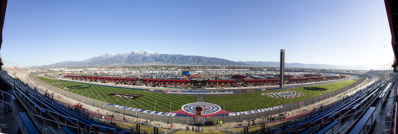 Fontana, CA / USA - 3/17/2019: A panoramic view of Auto Club Speedway prior to the Auto Club 400 Mountain Stadium Sport Sky Blue Clear Sky Nature Day Transportation Competition Architecture High Angle View Motorsport Road Outdoors Crowd Mountain Range Mode Of Transportation Sports Race People Motor Racing Track Spectator Auto Racing Panorama Panoramic Raceway Race Track Speedway Grass Morning Sunrise Sports Grandstand