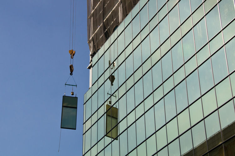 Low Angle View Of Crane Lifting Window By Building In Construction Against Sky