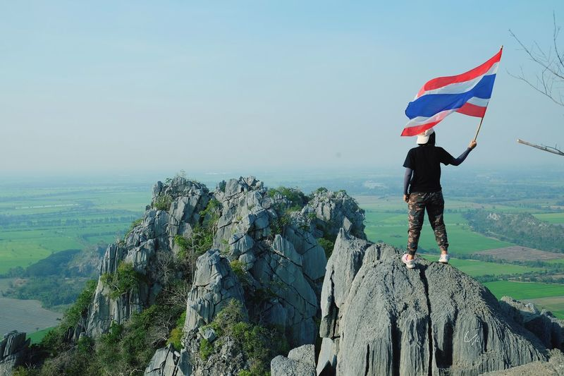 Rear view of woman holding thai flag while standing on rock against sky
